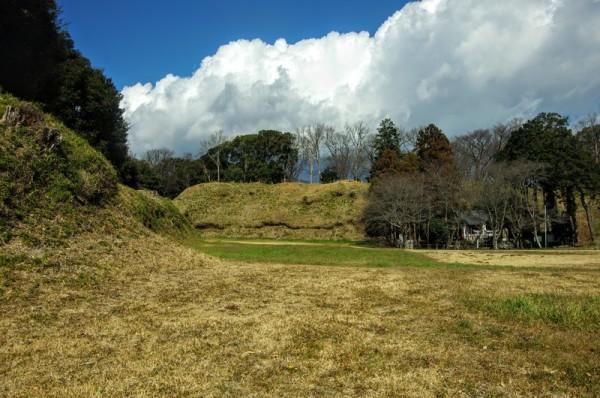 本丸西側と北側に残る土塁と、右奥には穂見神社が建つ