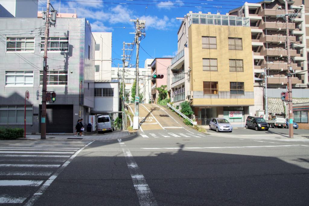 大阪女学院が建つ丘陵をかっての南惣構堀南であった長堀通りから高低差が残る坂を眺めたところ